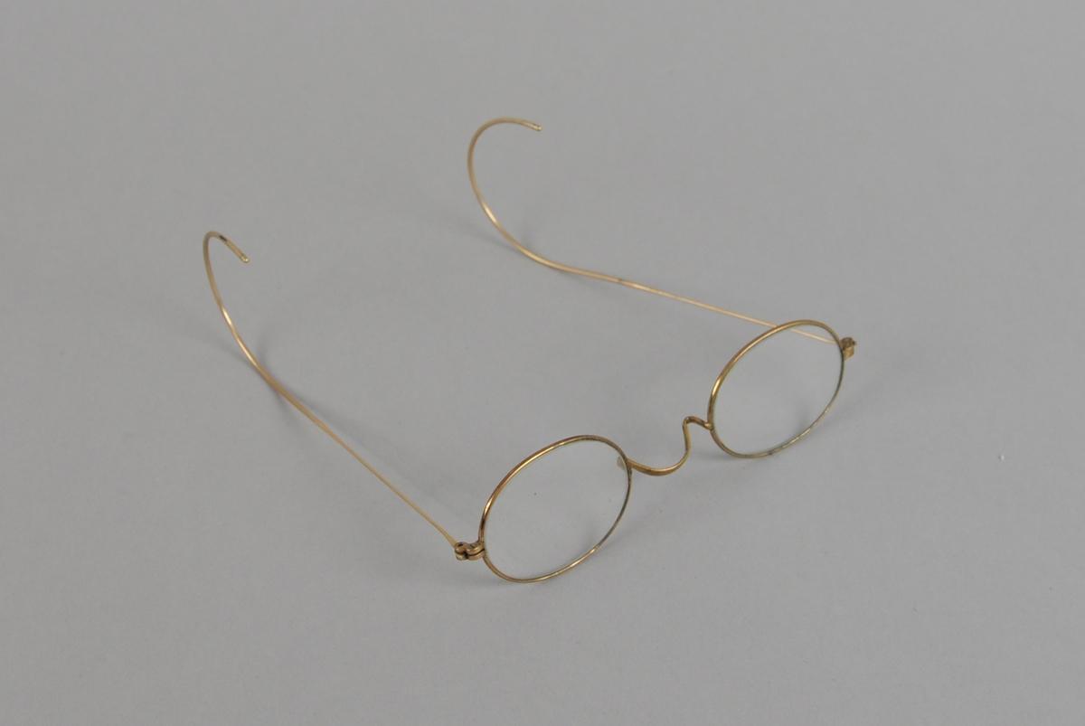Ovale briller med gullfarget metallinnfatning og buede brillestenger.