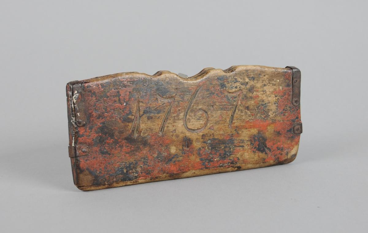 Brilleetui av treplater som er satt sammen av metallplater og spiker. Det er skåret inn initialer på den ene siden og årstall på den andre.