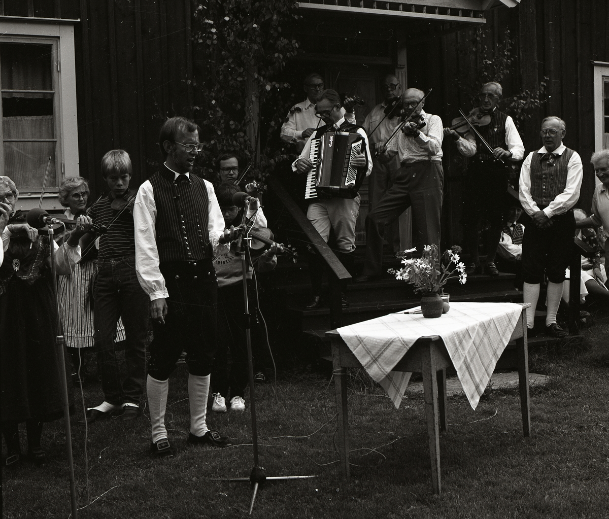 Ett spelmanslag samt en sångare upptäcker vid Rengsjöfesten, 18 juli 1982.