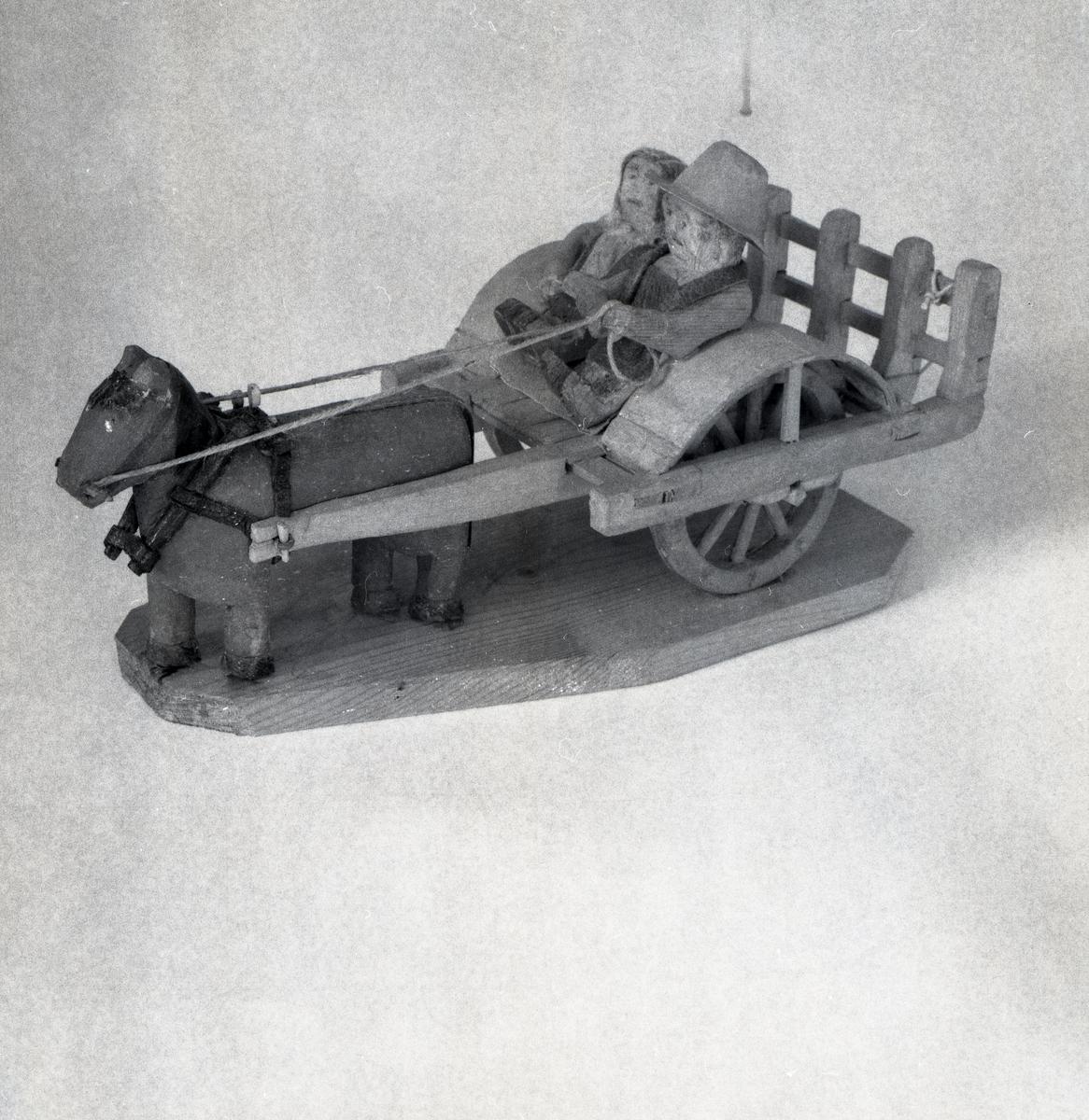 En trämodell av häst med vagn där två personer sitter i vagnen.