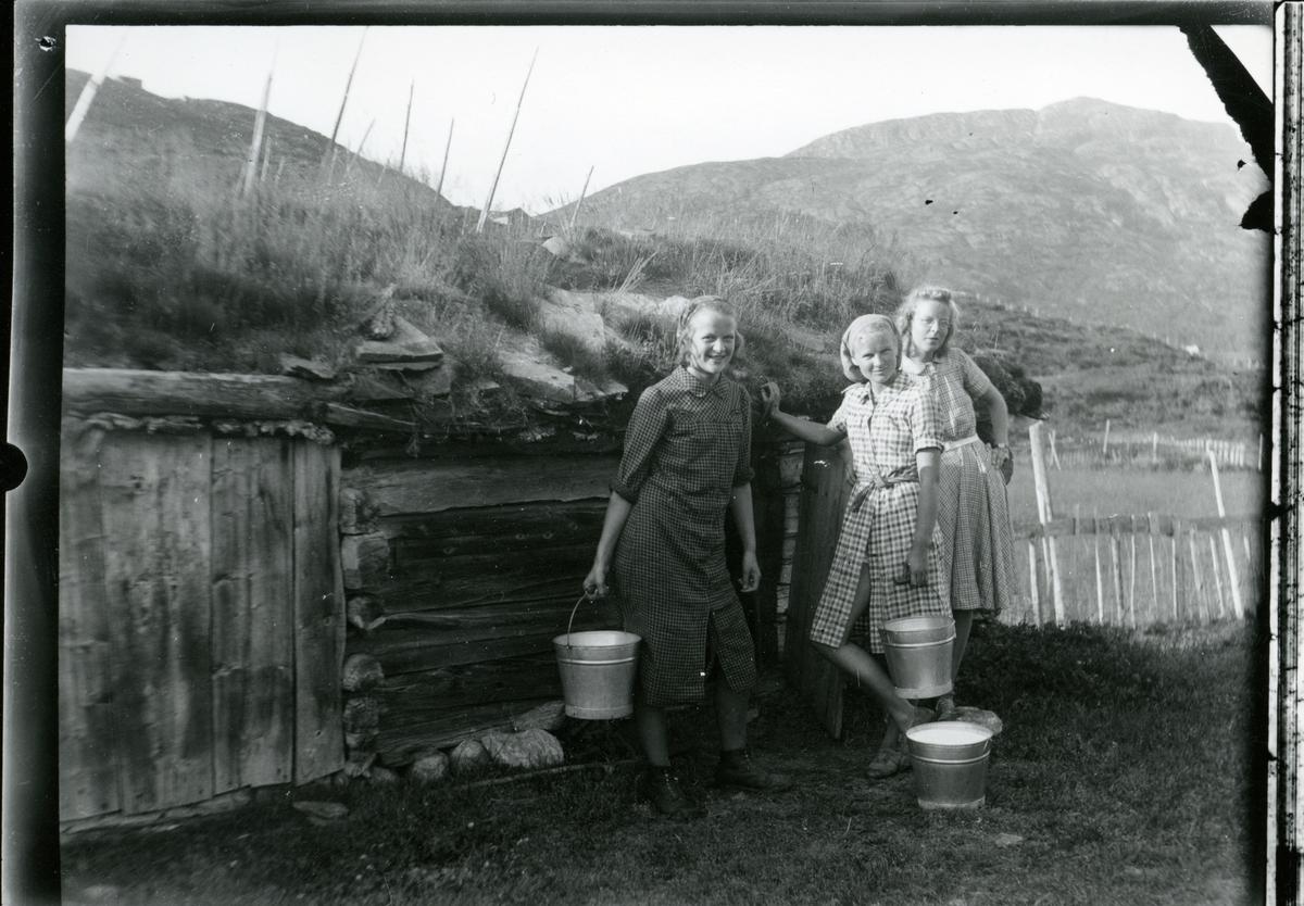 Tre unge jenter foran et stølsfjøs. De har fulle melkebøtter, og alle har forklekjoler.