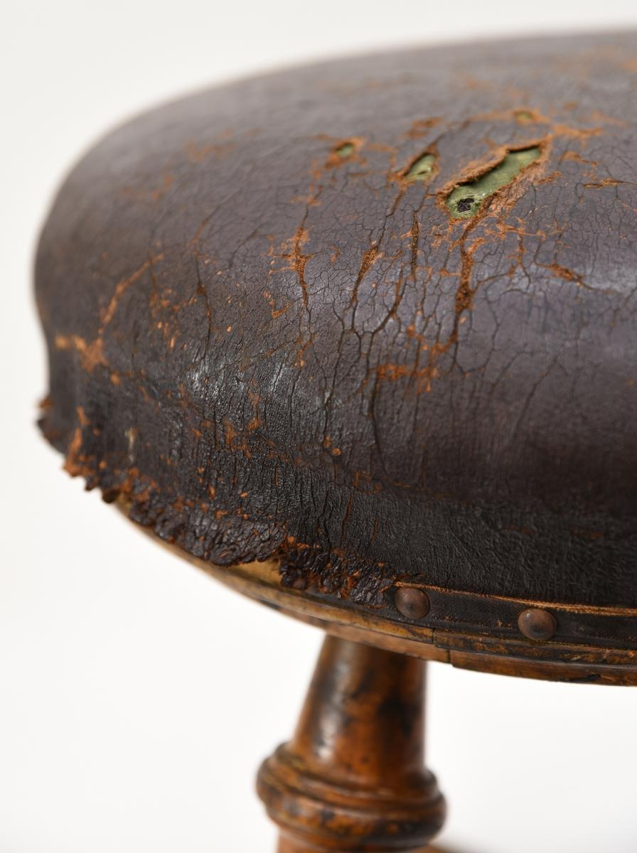 En trebent pall av trä. Benen är sammanlänkade med stag och benen har dekorativa svarvade element. Pallen är försedd med en läderövertäckt dyna, dynan är stoppad med tagel eller kanske halm med ett grönt textilt överdrag.  Dynan har i sin tur ett brunt läderöverdrag som är fastspikat på träbritsen. Det finns många spikhål längs britsens kant vilket antyder att överdraget av läder kan ha bytts ut eller tillkommit i efterhand.