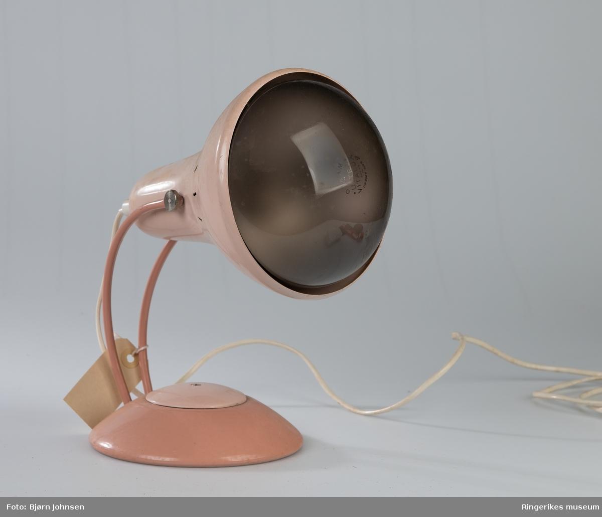 Lampe på lav bolleformet sokkel, to tynne rør  festet med skruer og muttere og forbinder sokkel og lampeskjerm/kapsel med hverandre. Lampeskjermen er traktformet. Stor lyspære med høy varmeeffekt er montert. Lang elektrisk ledning med kontakt.