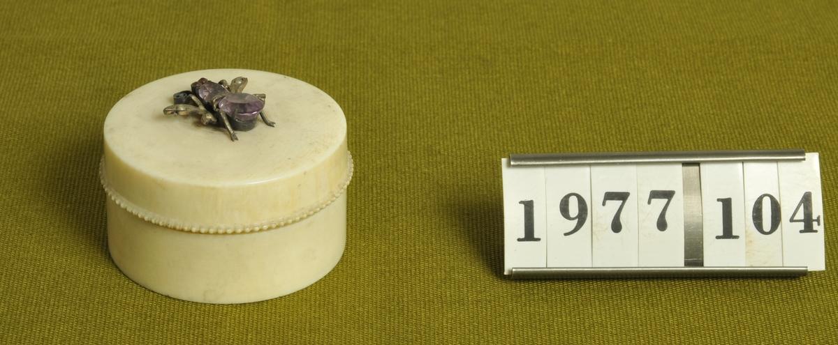 """Rund. Med lock. Locket prytt med en insekt av silver och slipade stenar. I botten inristat: """"Svarfvad af C. Adelsköld 1902""""."""