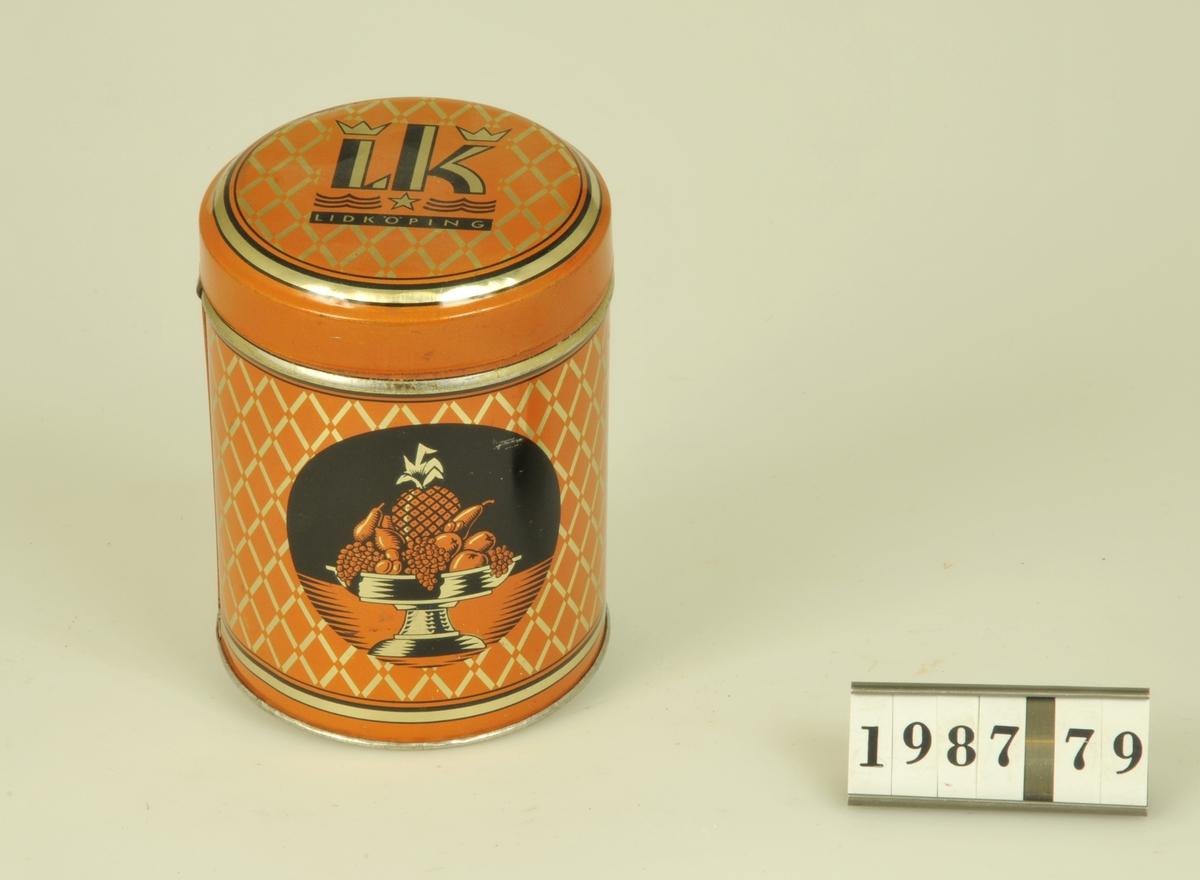 Rund form. Orange bottenfärg med svart text: LK LIDKÖPING TUTTI-FRUTTI Pris 50 öre Aktiebolaget Lidköpings Konfektyr Industri Lidköping på ena sidan. Motsva- rande sida med dekor i form av fruktfat på fot med ananas, päron och vindruvor.
