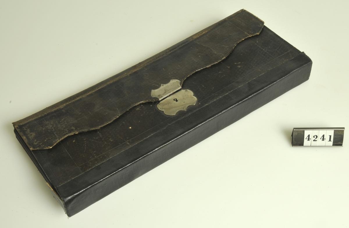 Av svart papp i väskform med lås och nyckel. Fack med månadsindelning.