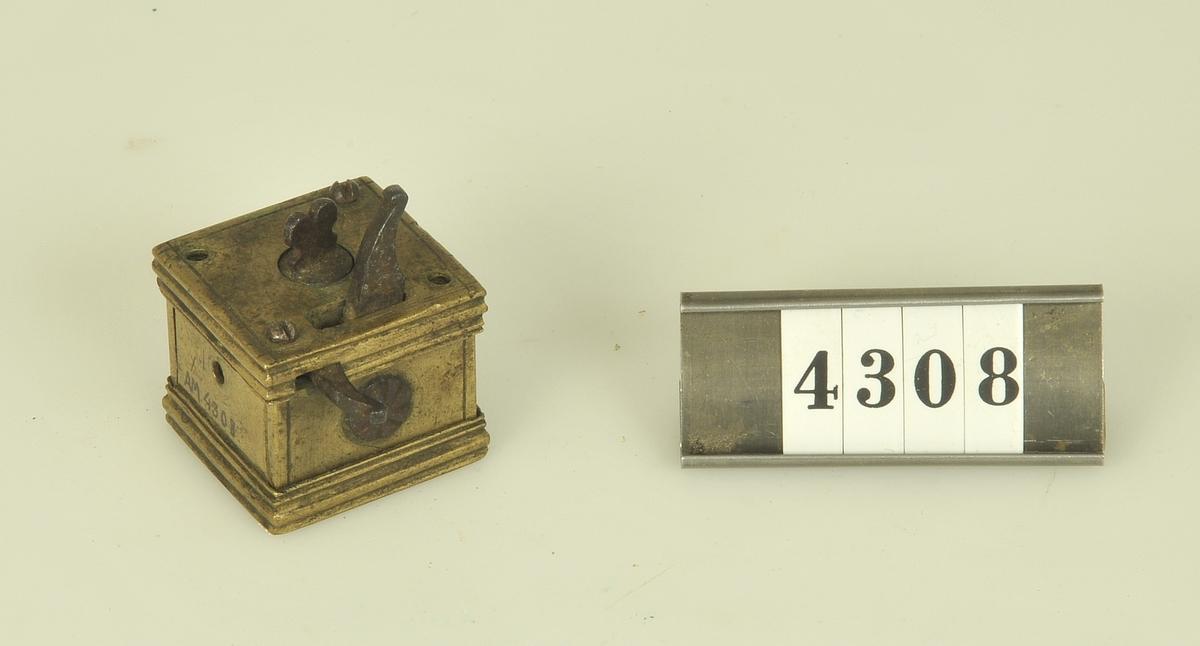 En kub av mässing med fjädermekanism. I botten öppningar för 13 små knivblad.