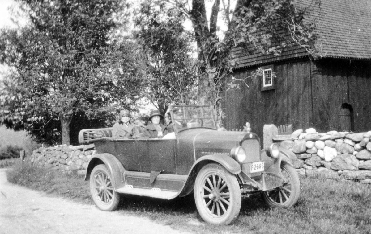 Anna Norlander på biltur med kvinna och en manlig chaufför sitter i en personbil utanför Stavkyrkan i Hedared. Bilen, med registreringsnummer P2686,  är en Star 1924 och står parkerad framför en stenmur.