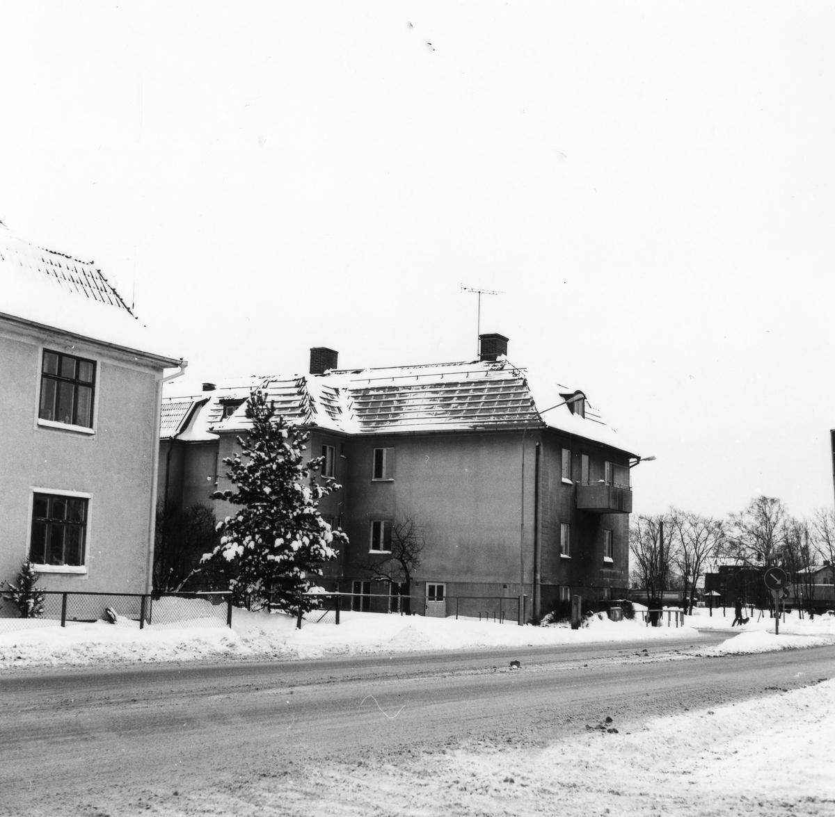 Vinterbild på snömoddig väg med 2 st bostadshus i centrum på bilden  Hörnet av Vänersborgsvägen och Kungsgatan, kv Fruktkorgen 16. Fastigheten fick rivningsbeslut november 1978.