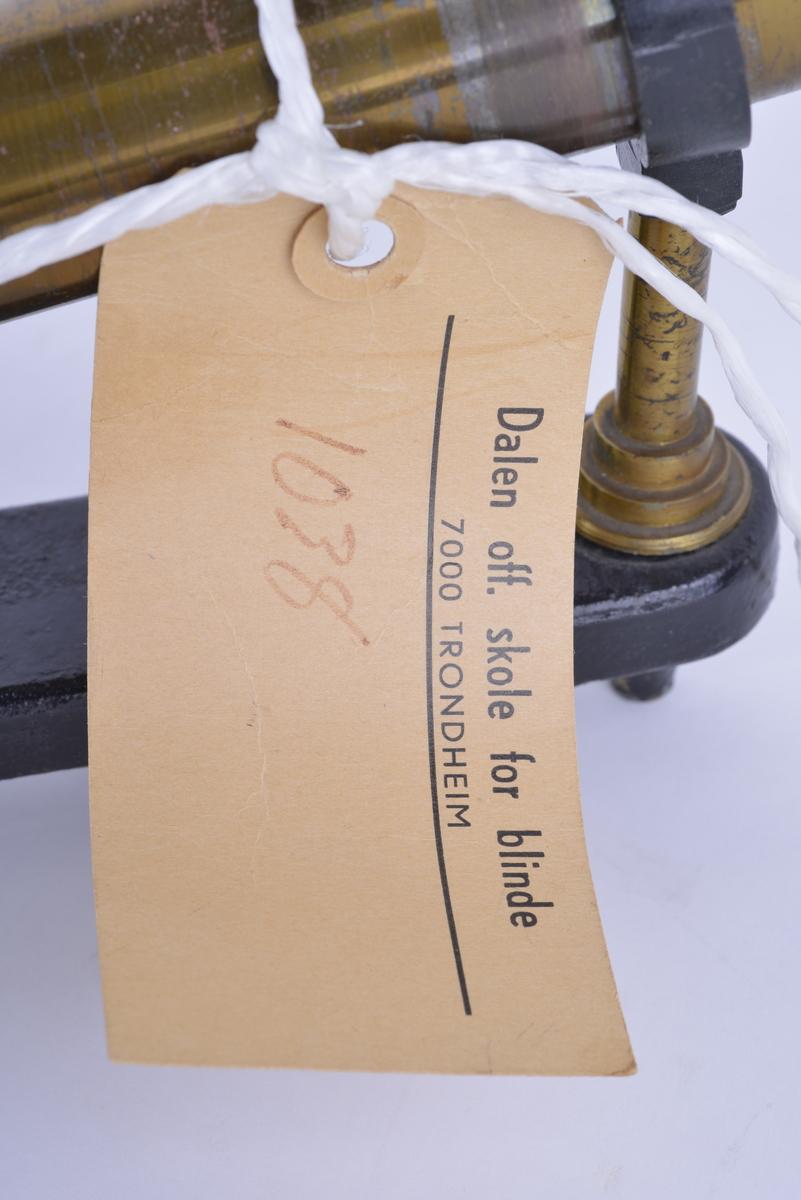 Manuell vakuumpumpe i messing. Pumpa er plassert over og langs en fot av støpejern. Pumpa er forbundet til en sirkulær vakuumplate av glass. På toppen er det montert en kopp med hull i midten, av støpejern. Apparatet har tre bein. I forkant er det en metallplate med en skrue og to hull. Kan monteres fast i underlaget. Rundt messingpumpa er det festet en merkelapp med et nylonsnøre.