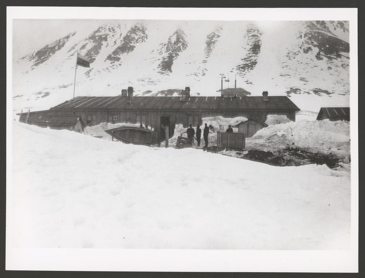 Bilden visar sannolikt den ryska övervintringsstationen vid Gåshamna, Hornsund på Spetsbergen. En låg träbarack ligger framför en brant berg. Framför husen står flera män som hantera olika föremål. Två av de har lagt en mindre roddbåt på sidan.