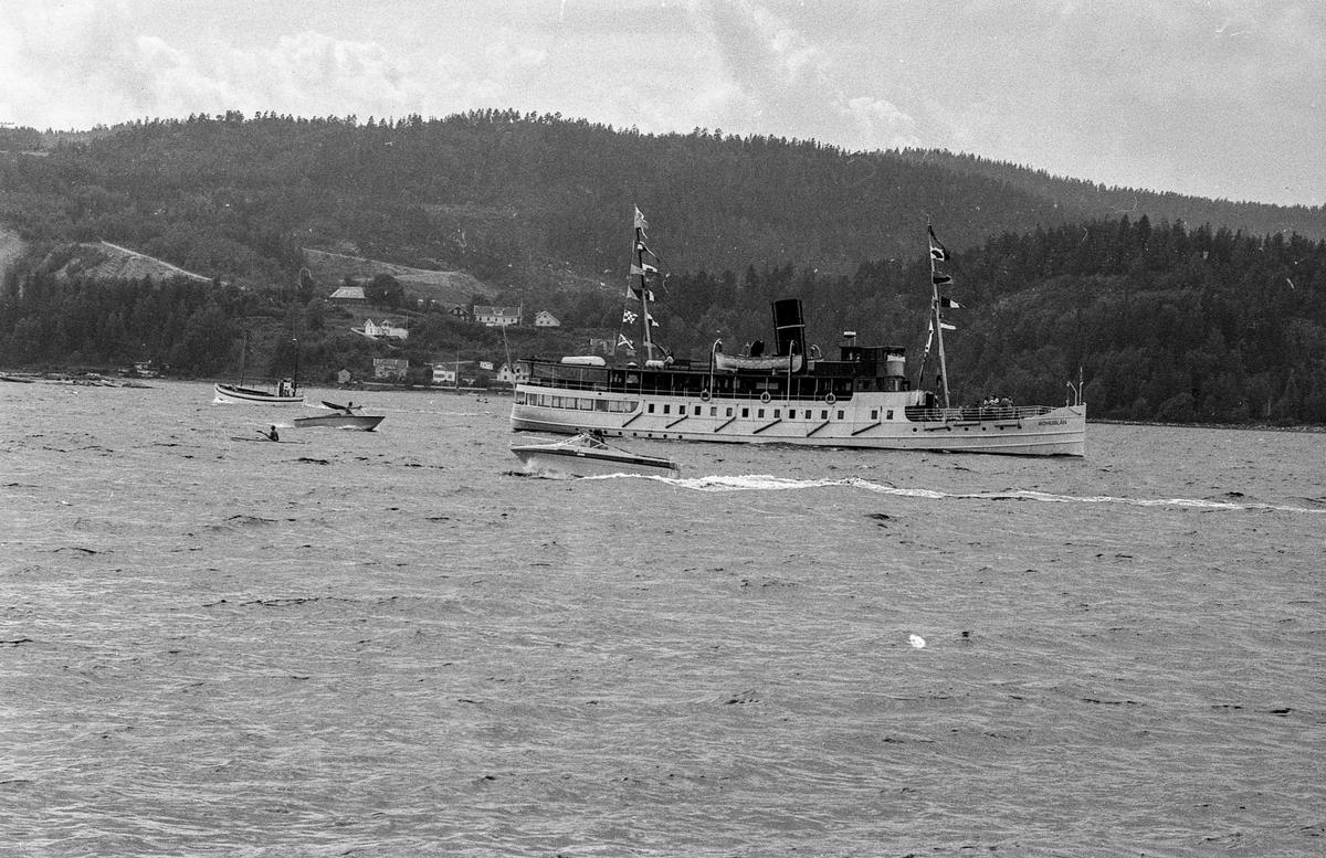 Drøbaksfjorden, sundet ved Oscarsborg. Tre menn på brygga ser på båtene med kikkert. Sandtaket og småhus på Hurum. Fotograf: ØB Rønning