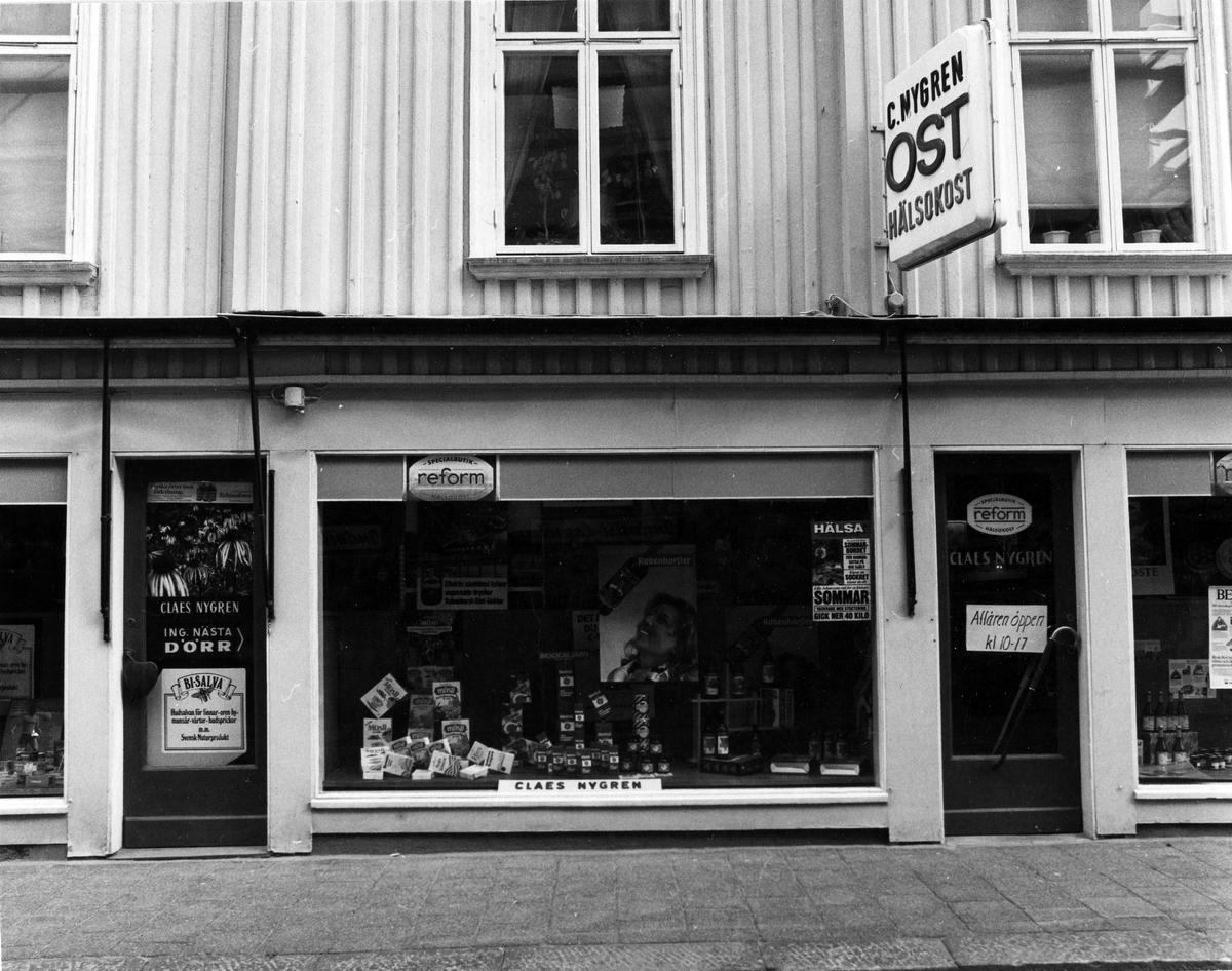 """Gatuvy av Claes Nygrens Speceriaffär. Ovanför huvudingången en skylt med texten """"C. Nygren Ost Hälsokost"""". Affären upphörde i september 1982. Kvarteret Pärlan 9."""