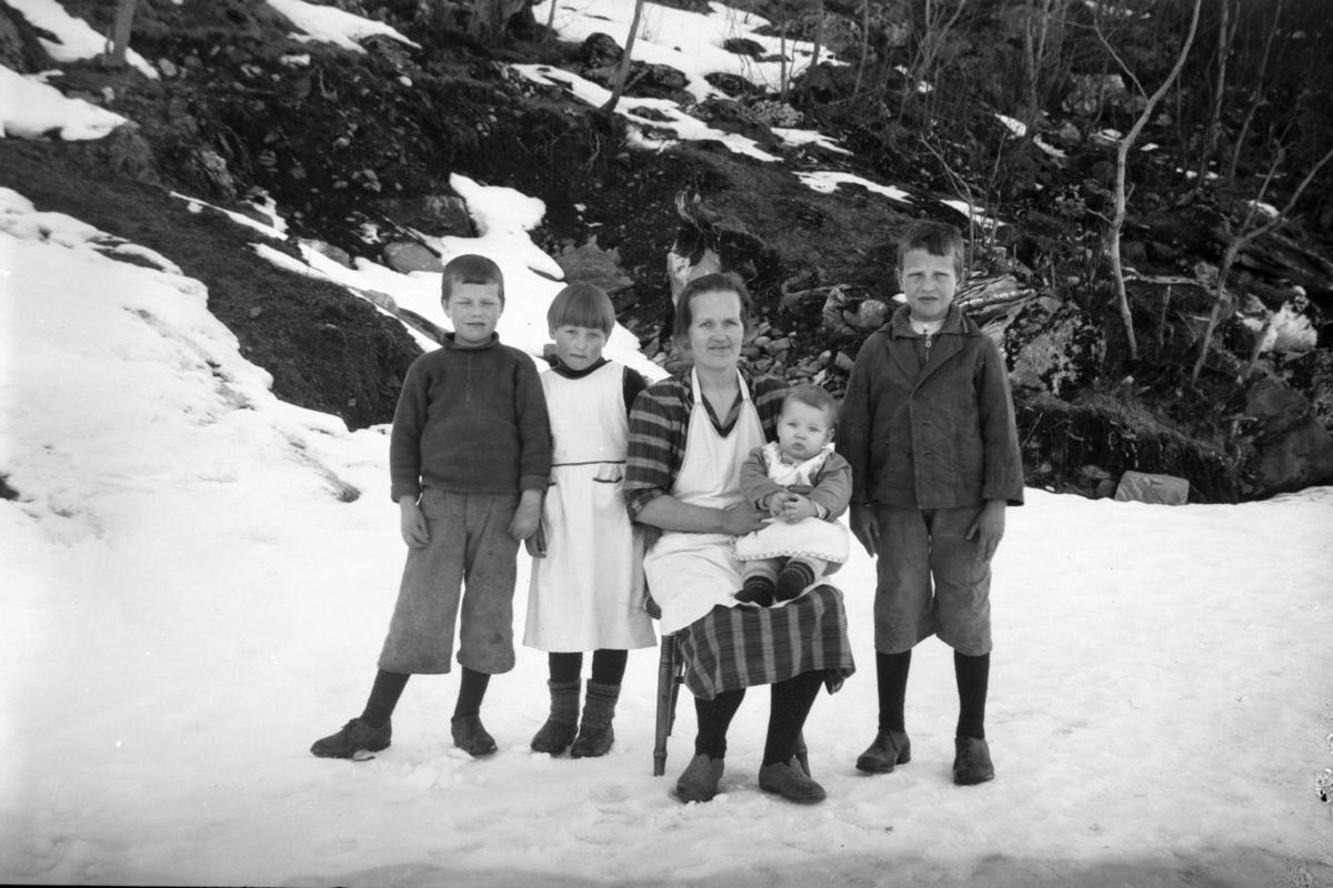 Gruppeportrett av kvinne med fire barn, tatt utendørs.