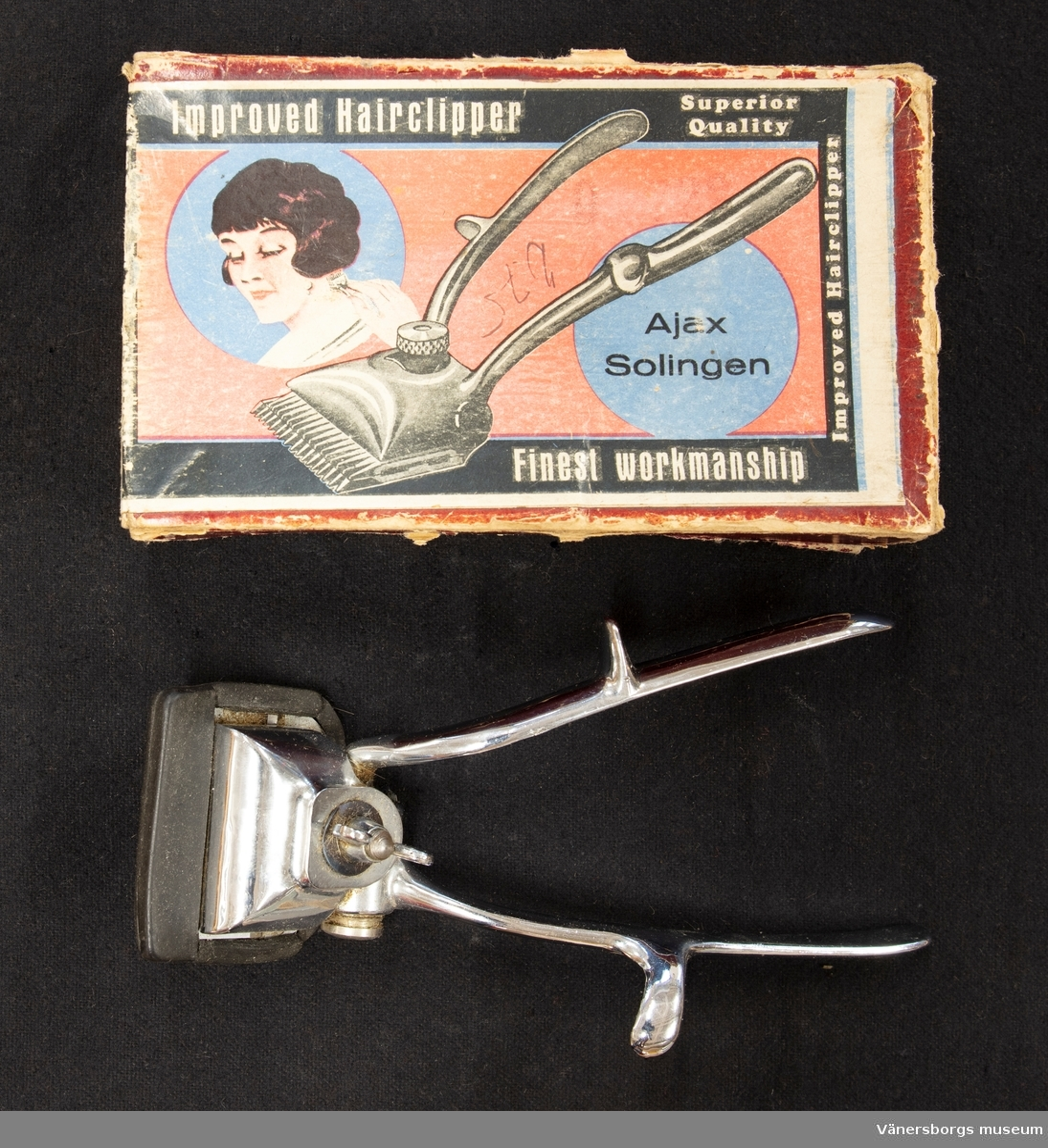 Handdriven klippmaskin med skydd för klippagregatet. Klippmaskinen ligger i en ask som är aningen för liten för maskinen.  Klippmaskin av stål i tre delar. Två byglar med utskjutande partier för greppbarheten. En löstagbar del som gör själva klippningen. På ena bygeln står Model No 146, Made in England by A. Marin&Co. Maskinen är försedd med ett gummiskydd för klippningsdelen.  Asken har en bild på en kvinna, en bild på maskinen och texten: Improved Hailcklipper, Superior Quality, Improved Haiclipper, Finest workmanship, Ajax Solingen.  Vid klippning för gesällprovet fick ingen klippning utföras med maskin, enligt givaren.