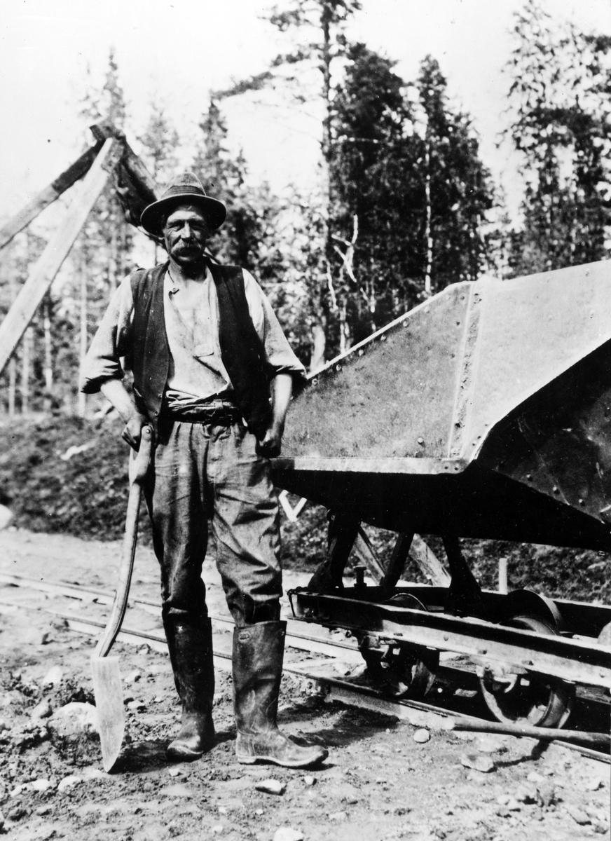 En rallare står vid sidan av rälsen med en tippbar järnvägsvagn vid sin sida. Troligen ej Alingsås.