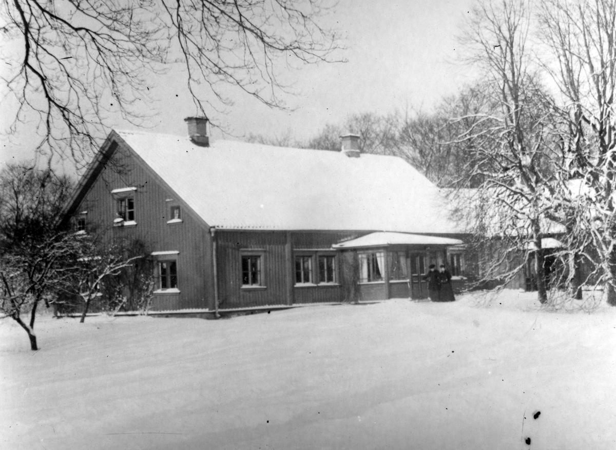 Gamla prästgården med ett snötäckt tak och marken likaså.
