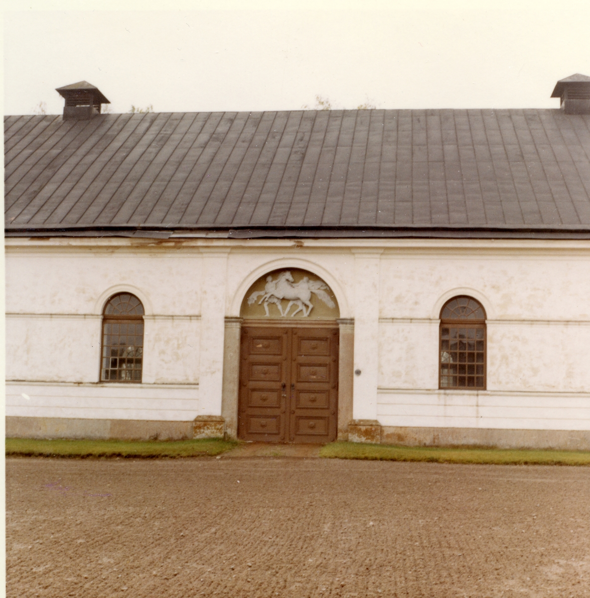 Kolbäck sn, Strömsholm. Ridskolan. Del av byggnaden, med rundade fönster och skulpterat dörröverstycke.