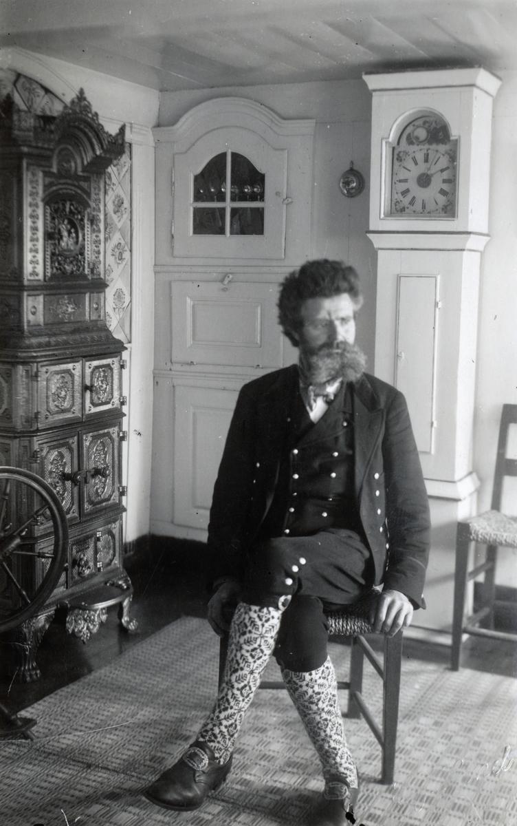 Portrett av Ingvald Skjeldrup kledd i nasjonaldrakt i hjemmet sitt på Ingebu, Søvik.