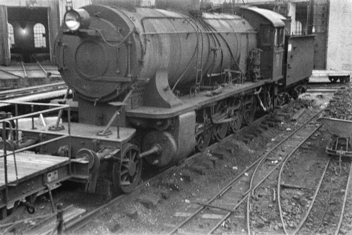 Utrangert damplokomotiv type 39a nr. 309 på Voss stasjon. Til høyre transportanlegg med vagger for kull til lokomotivene.