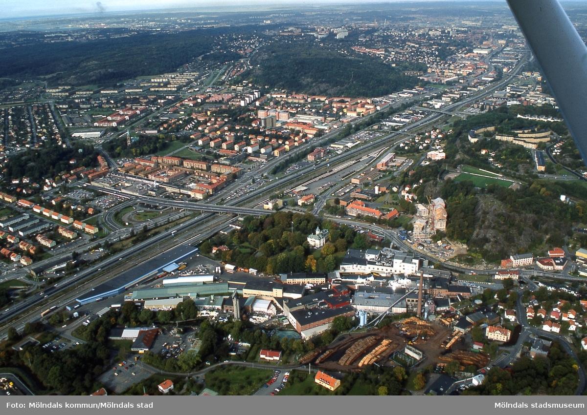 Flygfotografi över de centrala delarna av Mölndal, i september 1989. I förgrunden ses industribebyggelse tillhörande pappersbruket Papyrus samt Villa Papyrus med dess park. I bakgrunden till höger, hitom Kungsbackaleden, ses bebyggelse i Trädgården, Enerbacken samt vid Gamla Torget. Bortom järnvägen, Kungsbackaleden och Göteborgsvägen ses bebyggelse på Broslätt, i Mölndalsbro, Solängen, Bifrost, Toltorp, Bosgården och Krokslätt. I fonden ligger staden Göteborg. D 16:3.