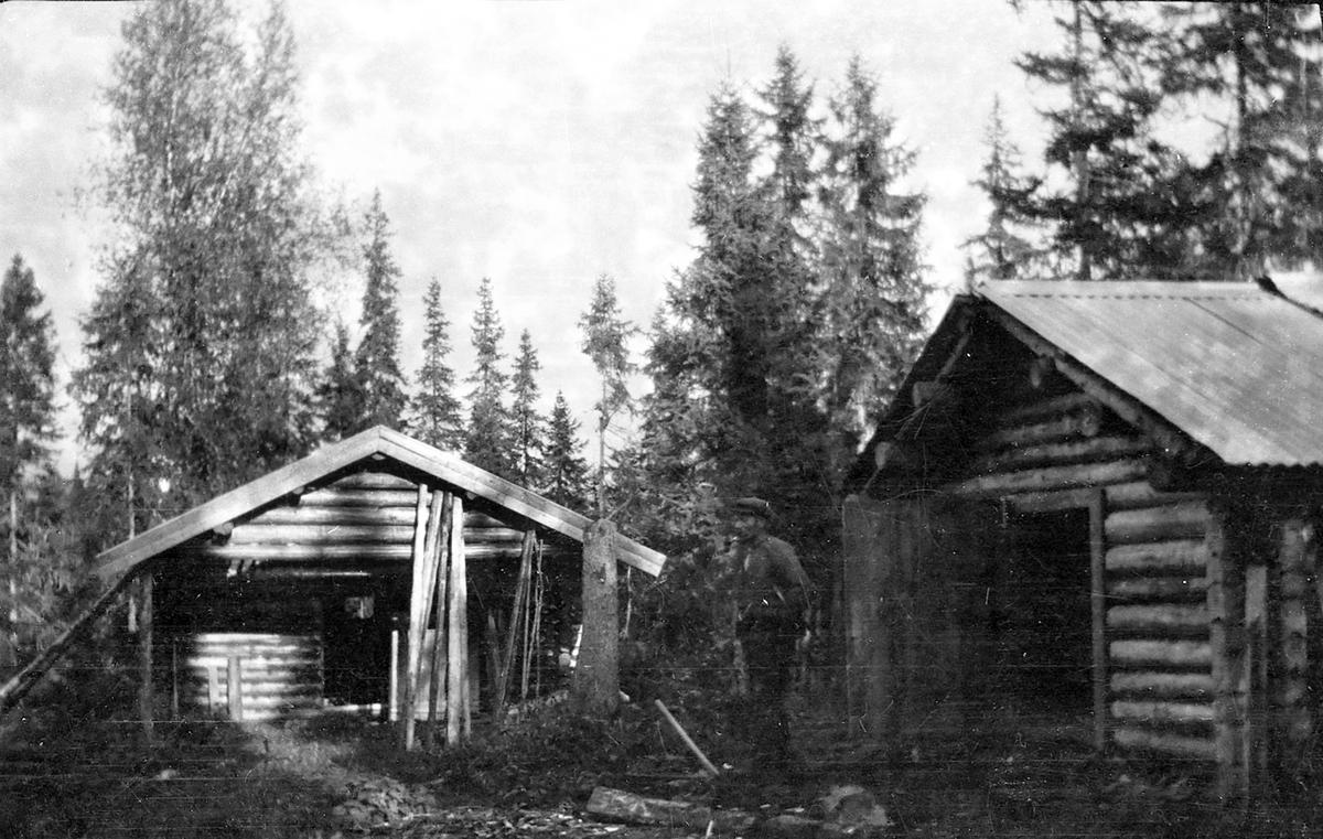 En mann ved to tømmerhus i skog.
