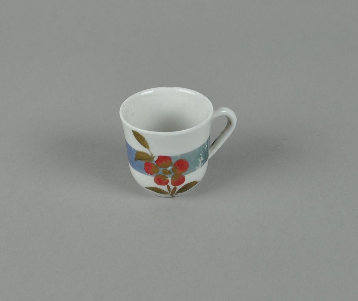 Kopp av glassert keramikk. Koppen har malt dekor av blå stripe og røde blomster. Koppen har hank.
