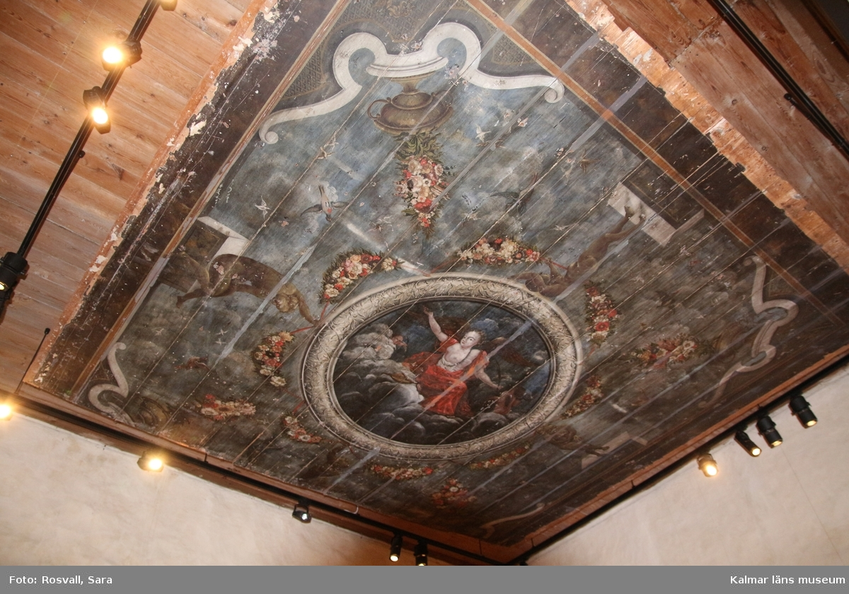 Mittpartiet framställer en kvinna på moln, (allegori?) inom rund ram som betsår av målade blad och bär av lager, däromkring breda blomstergirlander.