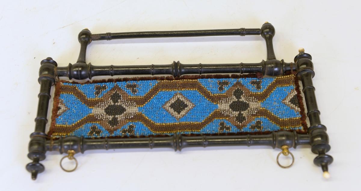 Handdukshängare med pärlbrodyr i blått och brunt inom svart träram med svarvade detaljer.
