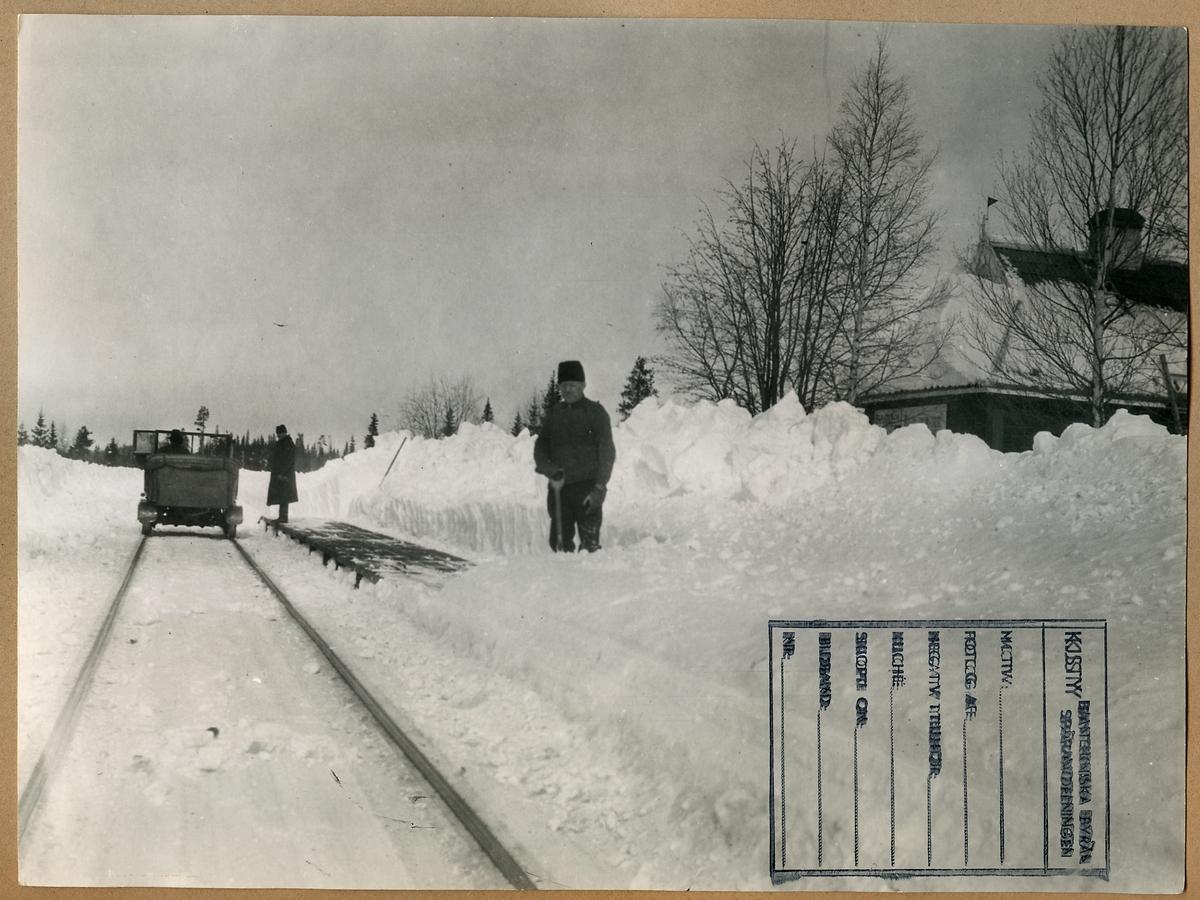 """Snöskottning av plattform vid Gråtbäck Station. Längre bort en motordressin, så kallad """"bil-dressin""""."""