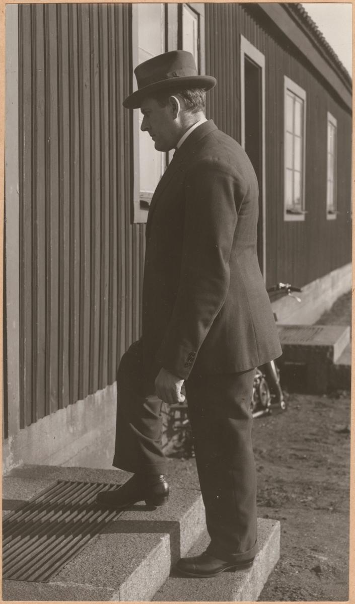 """Fotografi från """"Redogörelse för tillverkning vid Statens Järnvägars protesverkstad i Nässjö"""", 1932. Man med dubbla benproteser går uppför trappa utan stöd."""