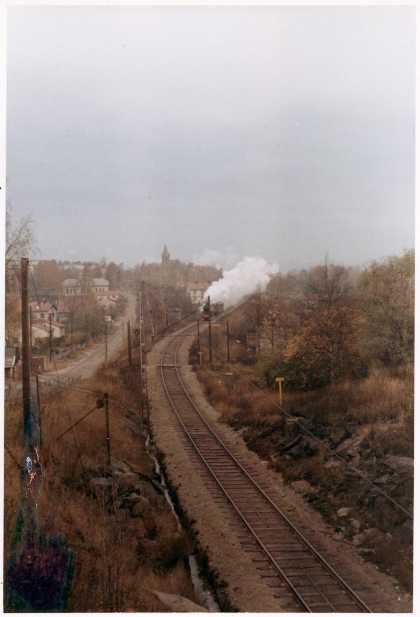 Statens Järnvägar, SJ F 1200.  Vy på järnvägslinje med trafikerande ånglok vid bebyggelse
