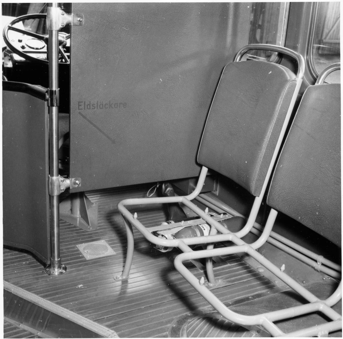 Interiör med förarplats, ofullständiga sittplatser och placering av eldsläckare i en buss.