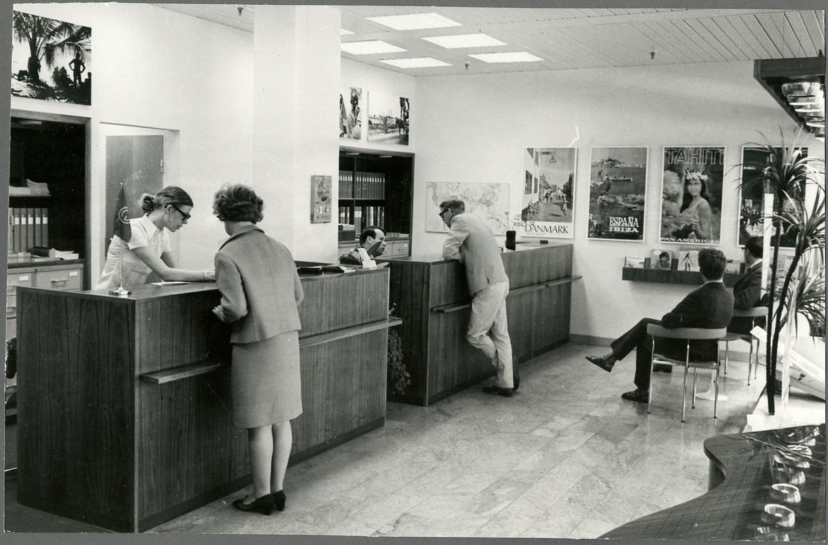 Interiör av resebyrå med personal och kunder.