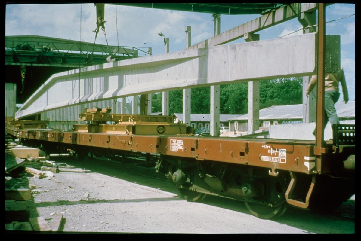 Lossning av betongbalk från godsvagn.