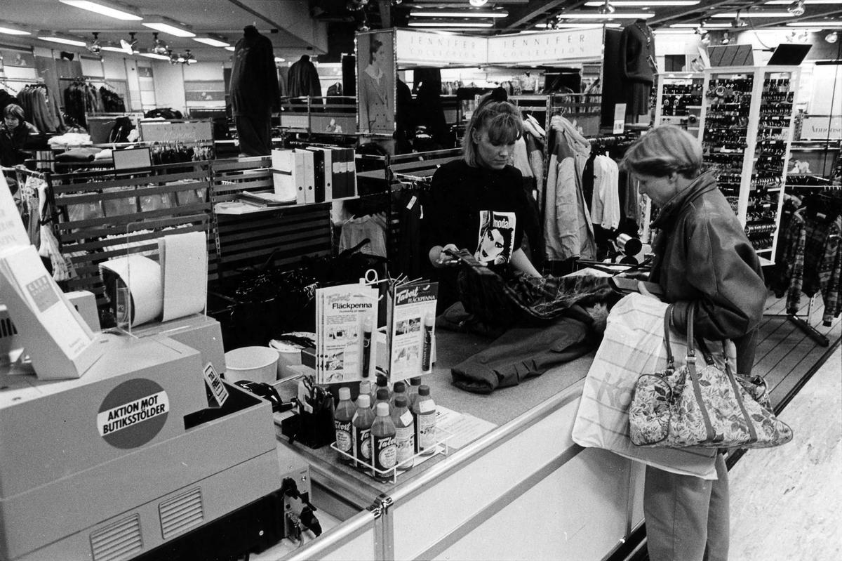 En kassörska hjälper en kund på Gulins, kvarter Hjorten 19. I november 1990 flyttade butiken tillsammans med Lindex in i Epas gamla varuhus i kvarter Storken 12.