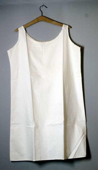 Av vit bomullslärft med vitbroderi i plattsöm. Monogram UL i plattsöm. Runt ringning och ärmhål langettstygn. Knäppt med en trådknapp på vardera axeln. Bruna fläckar.