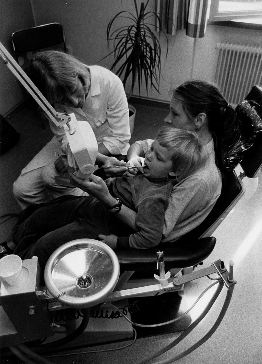 Ett barn sitter i en kvinnas knä under sitt första tandläkarbesök, Folktandvården i Alingsås.