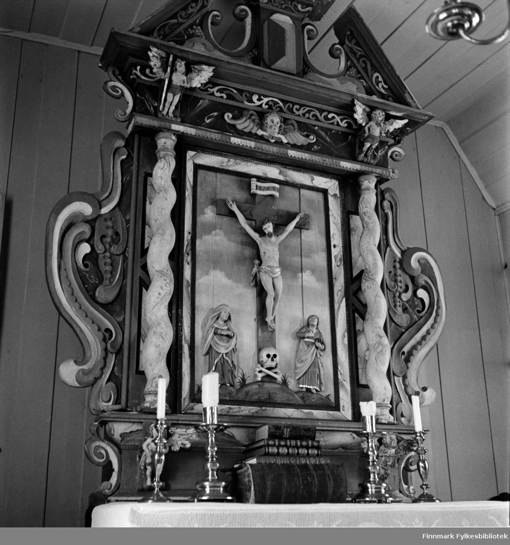 Kjøllefjord kirke 1940. Altertavle fra 1600-tallet. En historie sier at altertavla ble gitt til Skjøtningberg kirke av en takknemlig tysk skipper som ble reddet fra forlis utenfor Skjøtningberg. Altertavlen og flere andre gjenstander ble siden flyttet til gamle Kjøllefjord kirke når Skjøtningberg ble fraflyttet.   I bildet ser man også en stor gotisk bibel. Denne bibelen ble reddet fra brannen i 1944 da Hildur Hustad tok den med og flyktet til fjells. Bibelen oppbevares fortsatt i Kjøllefjord, i et brannsikkert hvelv.   Johan og Hildur Hustad fra Kristiansund, kom til Kjøllefjord i 1912. De holdt til på Sveenbruket på vestsiden i to år inntil bruket i Kluben ble ferdig. Der var det kai, egnebu, pakkhus med salteri i underetasjen og bolig og kontor i 2.etasje. Ditto ett pakkhus med blant annet trandamperi og boligrom. Pakkhus nr. 3 ble bygd i trettiårene. Hjellbruk langs fjæra og oppe i fjellsida. Hustad solgte solar, parafin og smøreolje for Vestlandske Petroleumscompani. G. Robertsen styrte over både Hustad- og Sveenbruket. Senere ble også firmanavnet endret til G. Robertsen. I 1940 flyttet Hustad fra Klubben og overtok Sveenbruket. Johan Hustad døde i 1942.   Kjøllefjord kirke var bygd i 1738 og sto i Kjøllefjord frem til den ble påtent av tyske soldater 4.november 1944. Ironisk nok var det sin egen kulturarv tyskerne brente. Kirken lå i Kjøllefjord prestegjeld som ble opprettet i 1685, da Skjøtningberg prestegjeld ble nedlat. Mye av inventaret stammet fra Skjøtningberg krike. Sakrestiet hadde en altertavle med årstallet 1662 som viser nattverdens innstiftelse. Denne skal tidligere å stått i Omgang kirke. Den opprinnelige kirken skal være byd mellom 1668 og 1683 og var en liten kirke bygget av rundtømmer. I kirken fantes også to klokker, hvorav den ene hadde inskripsjonen «Eine gude klock hin ick genant, den hört meinen klanck tho bargen int landt des late ick mi nicht vordreten. Heinrich Meier tho Bremen de oldermand he heft mi laten geten 1608. Restene av kirkek