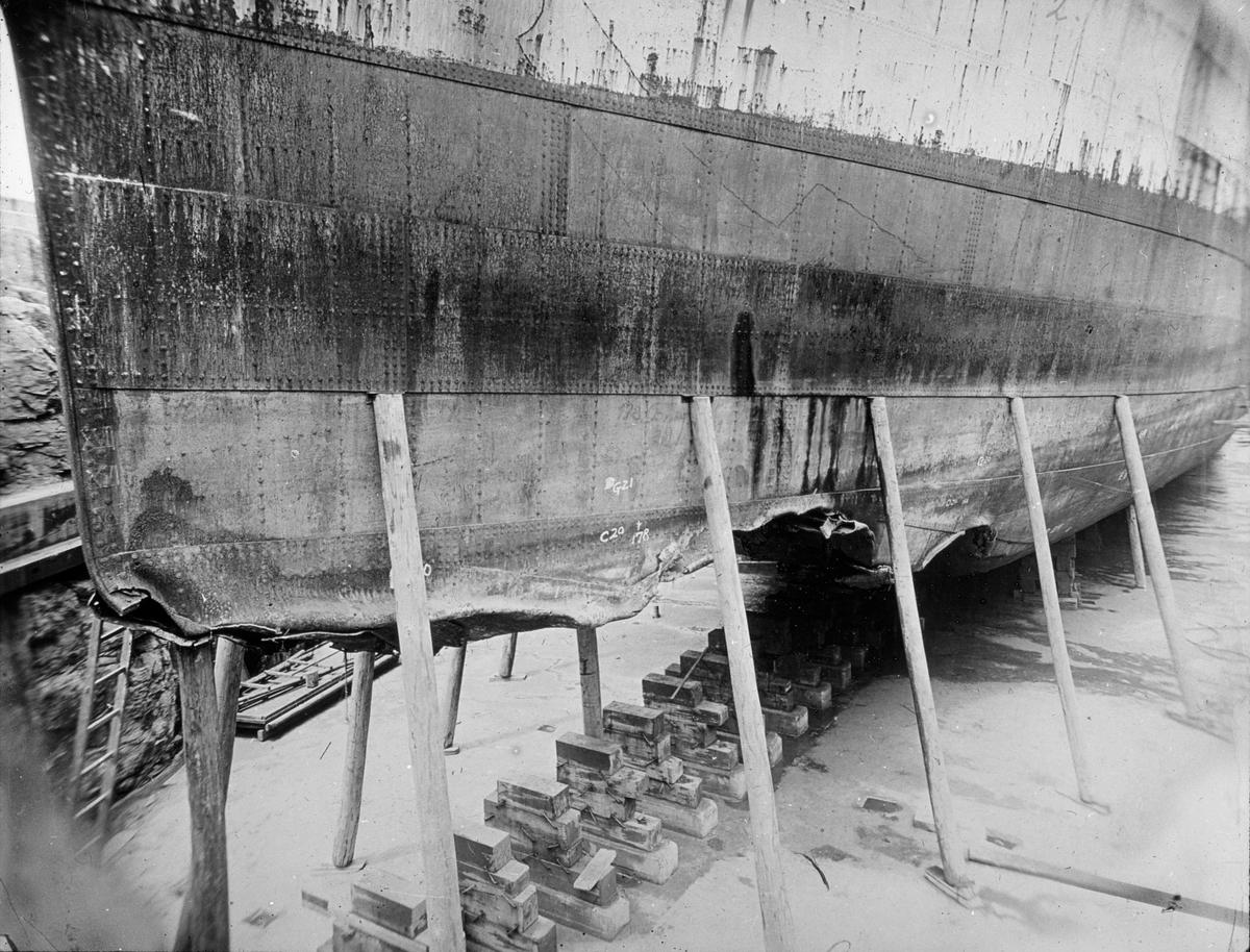 Skipsskrog i tørrdok. Skroget har vært satt på blokker, og er støttet videre opp på bjelker..