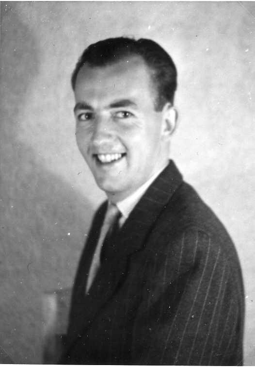 En man fotograferad från sidan, vänder sig mot fotografen och ler. Klädd i randig kavaj och slips.