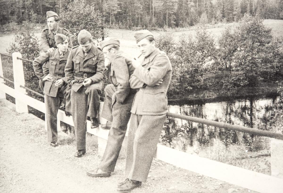 Norske polititropper står på en bro ved et vann eller elv i Sverige under 2. verdenskrig.