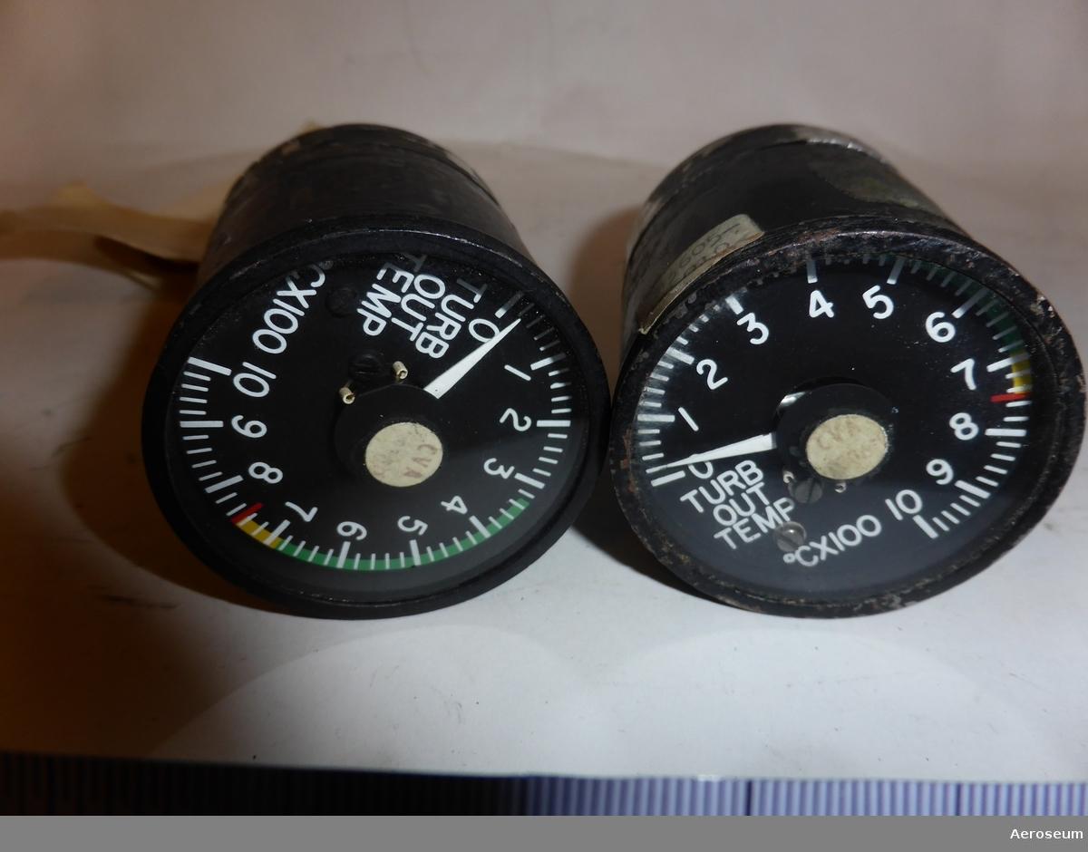 """Två stycken turbintemperaturindikatorer. Motorinstrument. Gjorda i svart metall.  På den ena av dem finns det en hängande ettikett där det står: """"LIR 52"""" och på andra sidan står det """"Important remove this shunt before connecting or fitting socket to instrument"""". Det finns också en fastklistrad ettiket där det står: """"T7409 1 HKP [går inte att tyda]"""". På botten av instrumentet står det: """"USE 8 OHM C.A. LEADS"""", """"SERIAL NO 1958"""", """"PART NO. 22-304-04"""", """"TEMP. IND. WESTON INSTRUMENT INC. WICHITA, KAN."""", """"F.A.A. TSO-C43 TYPE II WT. 1 LB.""""  På det andra föremålet står det på botten: """"USE 8 OHM C.A. LEADS"""", """"SERIAL NO 1796"""", """"PART NO. 22-304-04"""", """"TEMP. IND. WESTON INSTRUMENT INC. WICHITA, KAN."""", """"F.A.A. TSO-C43 TYPE II WT. 1 LB."""". Det finns även en påklistrad ettikett där det står: """"T74 [går inte att tyda]"""""""