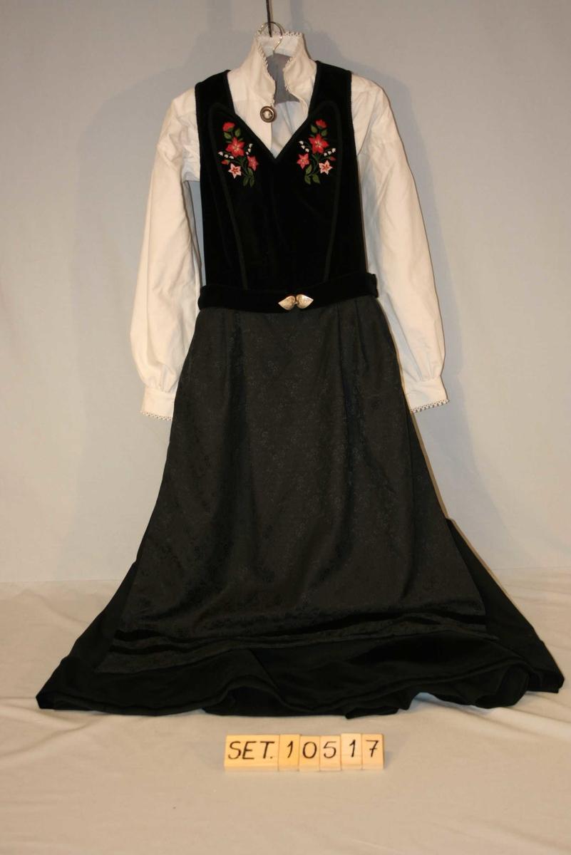Svart, fotsid stakk med svart forkle, brodert liv, belte og kvit bunadsskjorte