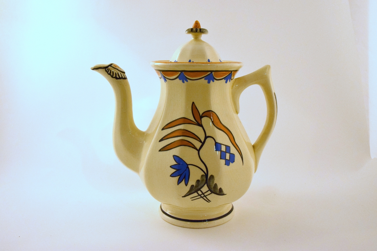 Kaffekanne til servise i off-white glasur. Dekor RAKLER: kantet  i gultt/blått/sort mønster. Midtstilt dekor i tilsvarende farger og grått.