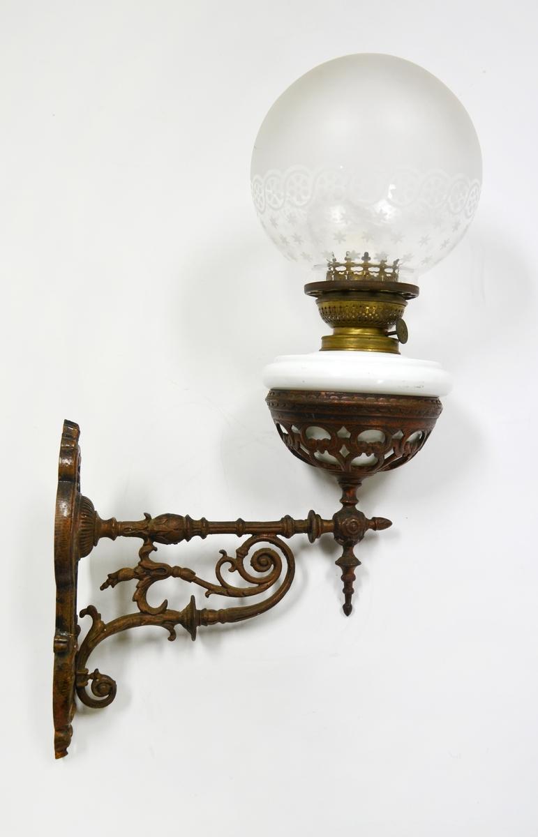 Oljelampe i metall,glass og porselen med veggefeste. Porselensskål til oppbevaring av olje og vekeholder. Lampeskjerm i mønstret glass.   Metallarmen er støpt i kobber/messing (?). I senere tid modifisert og tilpasset elektrisk strøm.