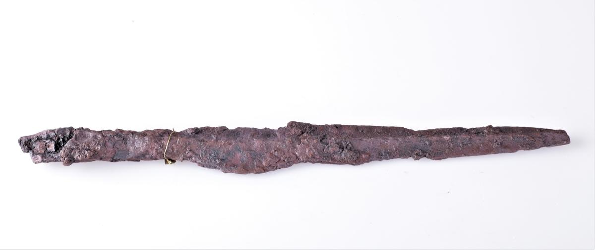 Spydspiss av jern med midtribbe, sl. Shetelig: Arkeologiske Tidsbestemmelser s. 9 fig. 8,. Fra yngre romersk jernalder og funnet i en gravhaug på Sukkestad i 1888.