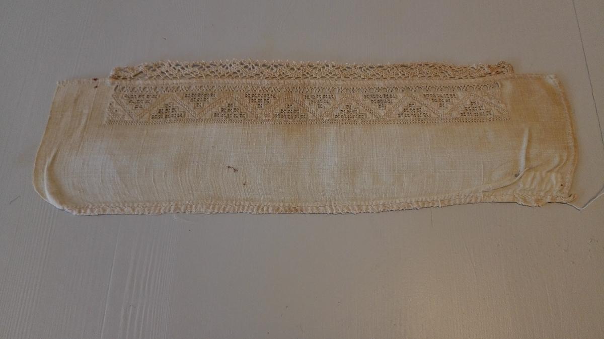 6354 - hyllik.  Stykke av en hyllik, 37 cm lang, med bredde nu 12 cm. Har en 3,4 cm bred hardangersøms lignede bord med en kniplet kant foran.  Gave fra Gjørand Skeie, Bruhjell, Balestrand.