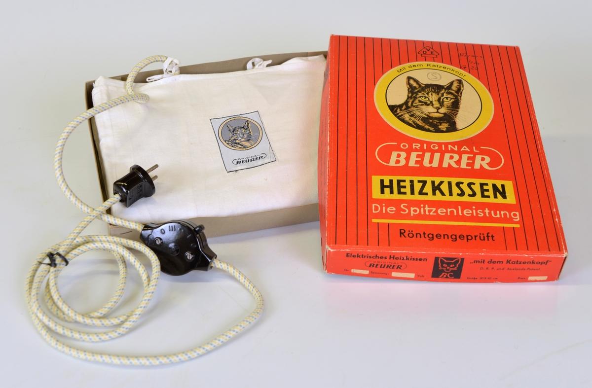 """Värmedyna av vitt bomullstyg. Reglage på sladden av bakelit. Värmen ställbar från 0 till 3. Doftar lavendel. Dynan är """"Röntgengeprüft"""".  Modell: Heizkissen"""