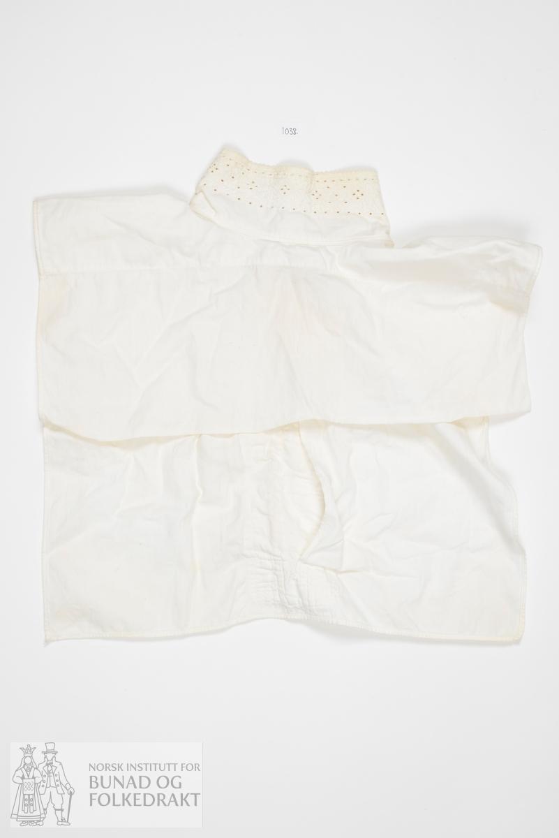 Skjortebryst av bomullslerret, all samansying sydd med maskin. Formklipt halsopning. Halssplitt mf, og utanpå delar av opningen er påsydd ei smekke, sydd med smale faldar med maskin. Lukking med knapphol og knappar. Halskvarden har kvitsaumsbroderi, sauma gjennom båe lag med stoff. Påsydd eit ekstra lag stoff på innsida over skulderpartiet, blir sauma fast i kantinga på kvar side. Lukking framme med knapphol og kvite perlemors-knappar.